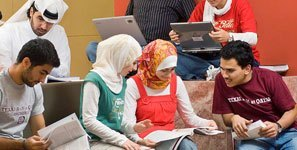 students in discussion, with laptops, notebooks and head coverings